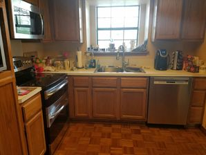 Kitchen cleaning by Clean Pro - woman cleaning kitchen cabinets